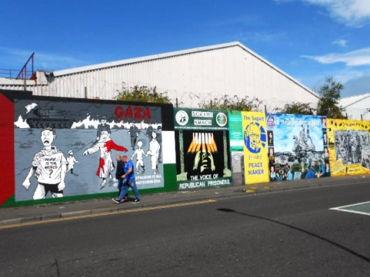 Men strolling past murals on The Falls Road